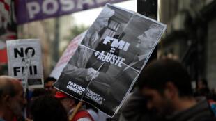 Militante argentino contrário ao empréstimo do FMI exibe cartaz de aperto de mãos entre a diretora-gerente do FMI, Christine Lagarde, e o presidente Mauricio Macri.
