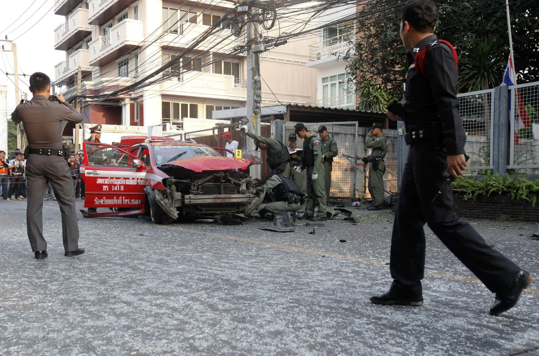 La policía inspecciona un automóvil dañado en el barrio de Ekamai, en el centro de Bangkok, el 14 de febrero de 2012..
