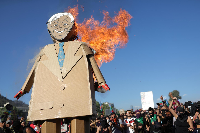 Manifestante segura cartaz representando o presidente chileno Sebastián Piñera pegando fogo durante manifestação em 29 de novembro de 2019.