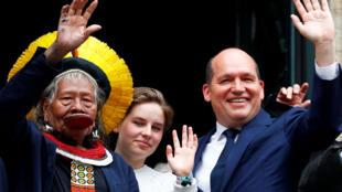 Raoni Metuktire, la militante belge en faveur du changement climatique, Anuna de Wever, et le maire de Bruxelles, Philippe Close saluent les gens depuis le balcon de l'hôtel de ville sur la Grand Place de Bruxelles, en Belgique, le 17 mai 2019.