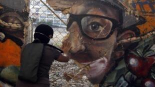 Manifestante destrói muro em praça de Caracas, na terça-feira 3 de março de 2014.