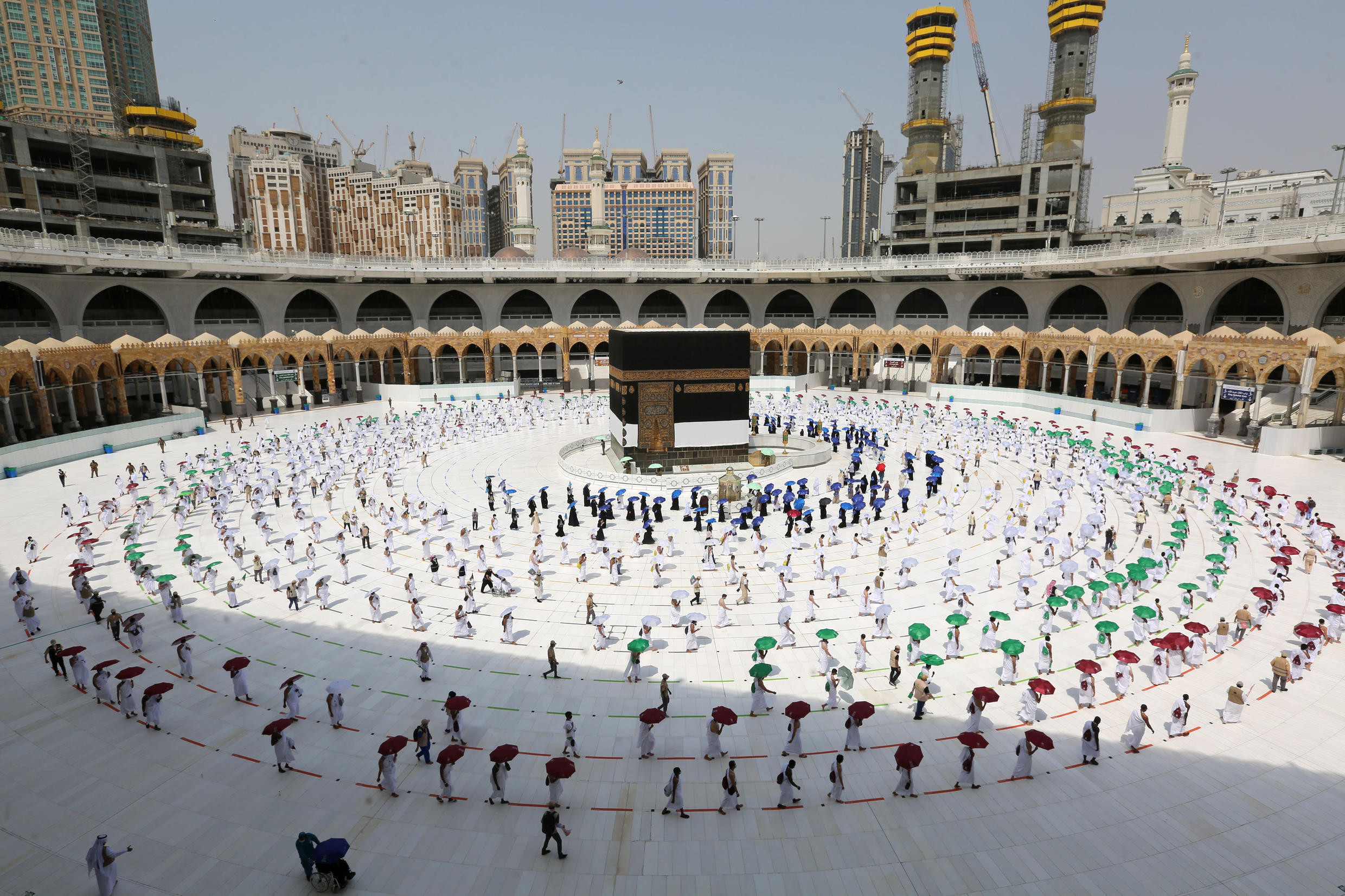 Pilgrims hold umbrellas and coloured rings as a measure against Covid-19 while circumambulating the Kaaba, Islam's holiest shrine, at the Grand Mosque in Mecca, at the start of the annual Muslim hajj pilgrimage in 2020