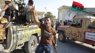 Des rebelles célèbrent leur entrée dans la caserne de Bab al-Azizia, QG de Mouammar Kadhafi, le 23 août 2011.