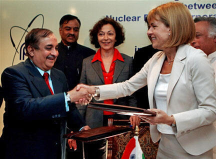 Anne Lauvergeon, head of French nuclear giant Areva, seals a deal as Anne-Marie Idrac, Minister of State for Foreign Trade, looks on.