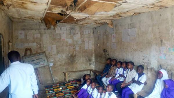 A Crossection of students in a damaged classroom in Nigeria.