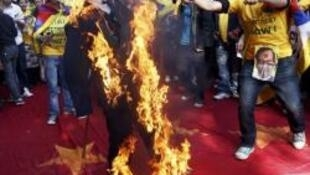 Tibetan exiles burn an effigy during a protest march against Wen Jiabao's visit to India, in New Delhi