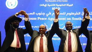 South Sudan President Salva Kiir (L), Sudan's President Omar Al-Bashir (C) and South Sudan rebel leader Riek Machar hold hands after signing a peace agreement aimed to end a war in which tens of thousands of people have been killed, in Khartoum, Sudan June