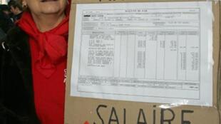 """Marsella: """"33 años de un trabajador venido a menos [con un] salario de miseria"""" se lee en el cartel de una manifestante."""