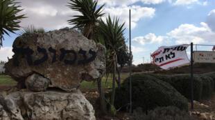 Un drapeau de la campagne de soutien à Amona a été accroché sur le bord de la route, à côté de la pierre annonçant l'entrée dans Amona.