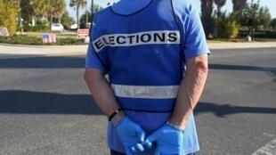 Un fonctionnaire électoral porte des gants pour se prémunir contre le virus lors de la primaire démocrate de The Villages, en Floride, le 17 mars 2020.