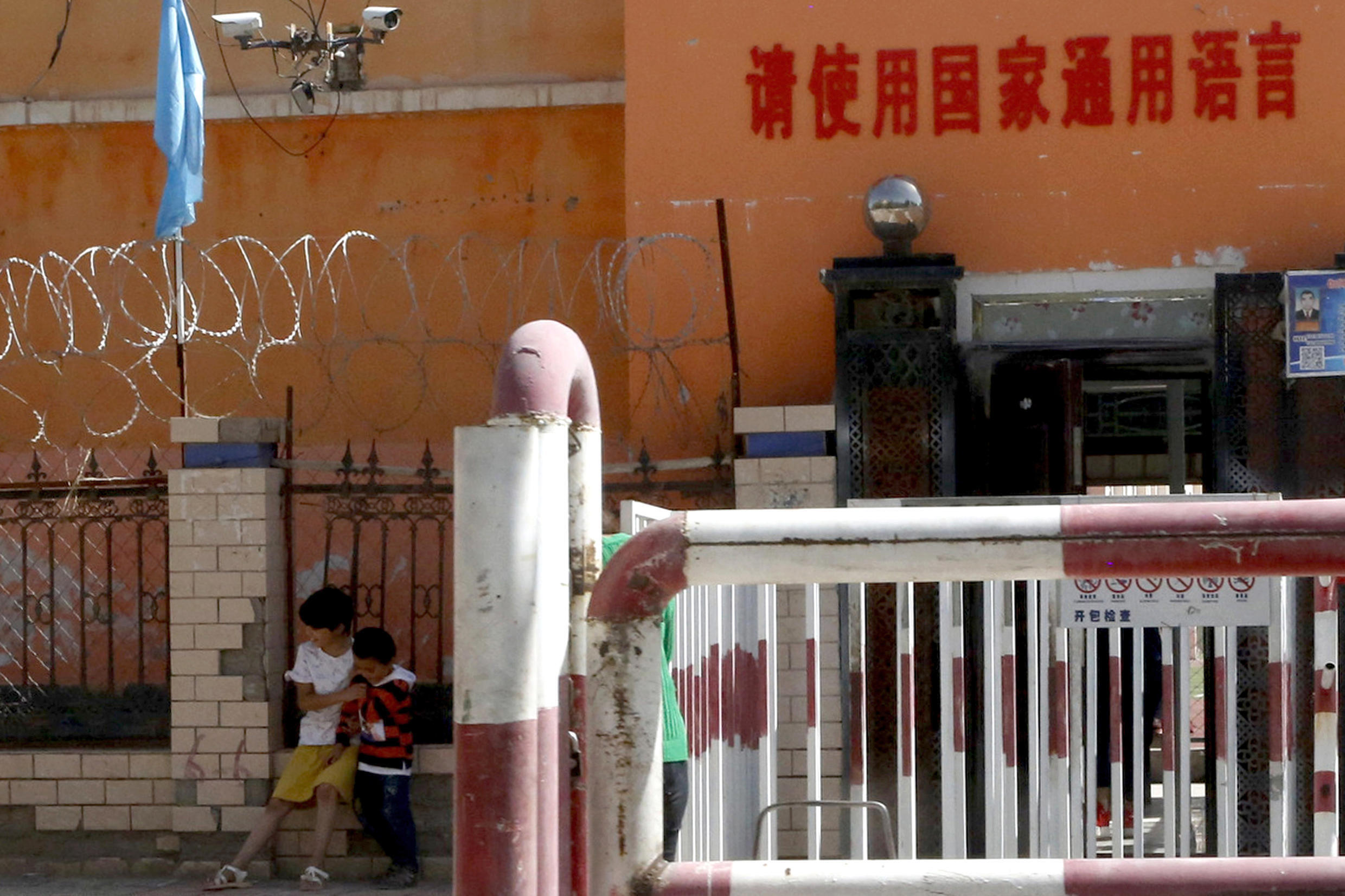 "In this Aug. 31, 2018, file photo, children play outside the entrance to a school ringed with barbed wire, barricades and surveillance cameras near a sign which reads: ""Please use the nation's common language"" indicating the use of Mandarin in Peyzawat, western China's Xinjiang region."