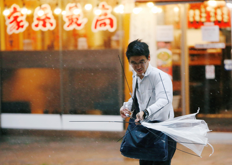 Um homem japonês luta contra o vento e a chuva às vésperas da chegada do tufão Jongdari, Tóquio, 28 de julho de 2018