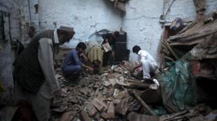 Un habitant de Peshawar, au Pakistan, tente de récupérer des affaires dans sa maison dévastée par le tremblement de terre qui a frappé la région ce 26 octobre.