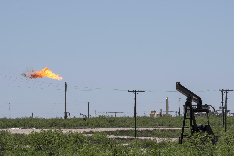 Una columna de fuego sale de una chimenea ubicada cerca de  otras infraestructuras de petróleo y gas el 24 de abril de 2020 cerca de Odessa, Texas