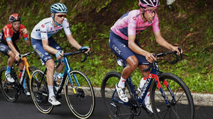 El líder de la general, el ciclista colombiano Egan Bernal (d), del equipo Ineos,  y el ciclista del equipo Astana, el ruso Aleksander Vlasov (C), en el ascenso final durante la 14a etapa de la carrera ciclista Giro d'Italia 2021, 205 km entre Citadella y Monte Zoncolan, el 22 de mayo 2021.