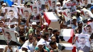 Des supporters de l'ex-président Morsi lancent des slogans et portent des cercueils symboliques, lors d'une manifestation au Caire, ce mardi 30 juillet 2013.