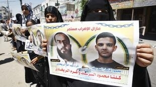 Palestinians hold posters depicting prisoners Mahmoud Al-Sarsak (R) and Akram al-Rekhawi during a rally in solidarity with them