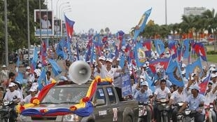 Supporters of the Cambodian People Party march along a street during an election rally in central Phnom Penh
