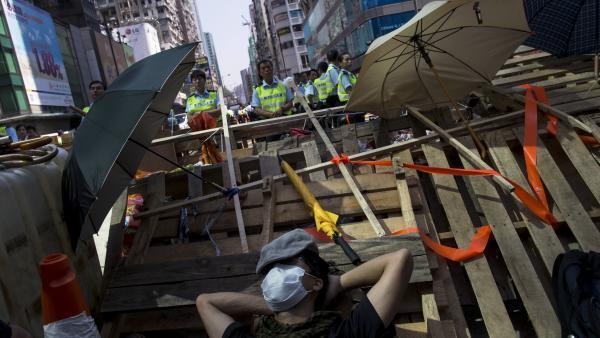 Um manifestante pró-democrático fica deitado diante da polícia em uma barricada no bairro comercial de Mongkok, neste sábado, 18 de outubro de 2014.