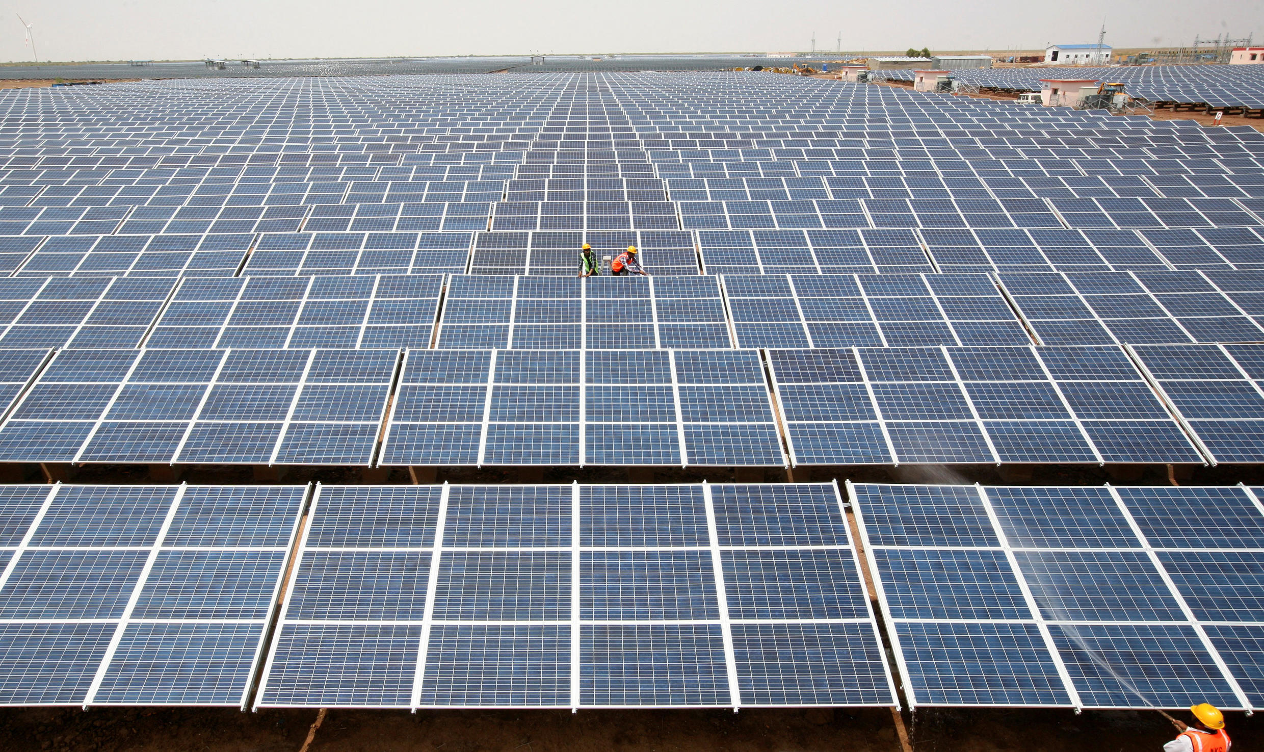 Workers install photovoltaic solar panels at the Gujarat solar park in Charanka village, Gujarat, India.