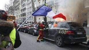 "A protester waves a French flag as a firefighter puts out a burning car tagged ""ISF"" (fortune tax) during a demonstration in Paris on February 9, 2019, as the Yellow Vests protesters take to the streets for the 13th consecutive Saturday,"