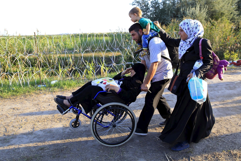 Une famille de migrants syriens parcourt le chemin qui longe le mur de barbelés érigé par la Hongrie à sa frontière avec la Serbie, le 29 août 2015.