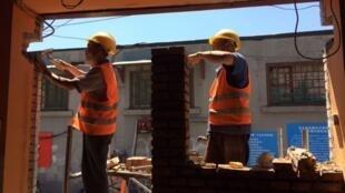 Des ouvriers à l'œuvre lors de travaux de modernistation urbaine dans le vieux Pékin.