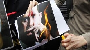 Una manifestante Sirio prende fuego a una foto del Presidente Bashar al-Assad en una manifestación contra el Gobierno Sirio en Estambul