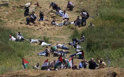 Protesters take cover as Israeli troops open fire near the Druze village of Majdal Shams in the Golan Heights Sunday