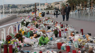 People walk past a memorial to the victims of the July 14 attack on the Promenade des Anglais, two days before a national tribute in Nice, France, October