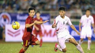 Một pha tranh bóng giữa cầu thủ Nguyễn Văn Quyết  (áo đỏ, trái) với cầu thủ Kim Kuk Bom của đội Bắc Triều Tiên trong trận giao hữu hôm 06/10/2016 tại thành phố Hồ Chí Minh. Tuyển Việt Nam thắng 5-2.