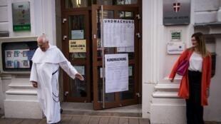 Un moine quittant un bureau de vote lors des élections législatives anticipées, à Vienne, le dimanche 29 septembre.