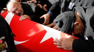 Mehmet Capat (esq.), pai de Yakup Capat, um policial turco morto em uma das explosões no sábado, chora abraçado ao caixão do filho durante funeral nesta segunda-feira (12), em Istambul.