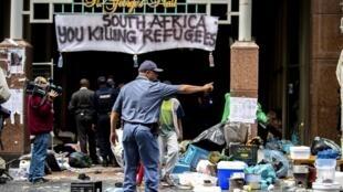 Des policiers sud-africains éloignent de force des réfugiés qui campaient devant les bureaux du Conseil des Nations Unies pour les réfugiés, le 30 octobre 2019 à Cape Town.