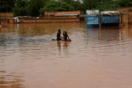 Des enfants dans une rue inondée par les eaux du fleuve Niger, dans le quartier Kirkissoye, à Niamey, le 27 août 2020.