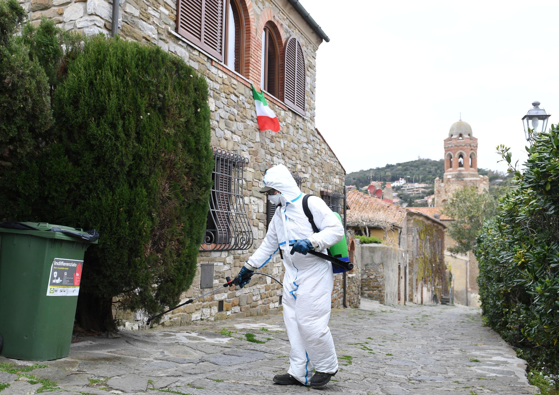 Nhân viên khử trùng khu thành cổ Castiglione della Pescaia, Grosseto, Ý, ngày 31/03/2020.