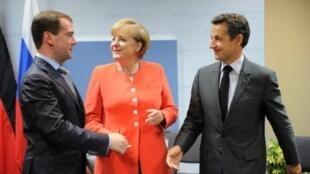 ពីឆ្វេងទៅស្តាំ៖ លោក ឌីមីទ្រី មេដវេដេវ (Dmitri Medvedev), លោកស្រីអង់ហ្កេឡា មែរកិល (Angela Merkel) និងលោកនីកូឡា សាកូហ្ស៊ី (Nicolas Sarkozy)