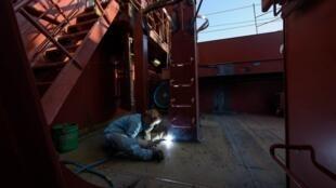 Un ouvrier métallurgiste travaille sur un porte-conteneur sur le chantier Daewoo d'Okpo, à 60 km au sud de Busan (Corée du sud).