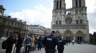 Policiais franceses patrulham o exterior da catedral de Notre-Dame enquanto as pessoas se preparam para assistir à missa da Páscoa, no dia 27 de março de 2016, em Paris.