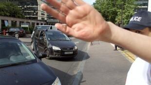 Policiais impedem a aproximação dos fotógrafos dos carros com os suspeitos.