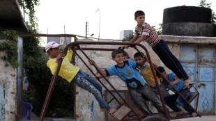 Des enfants jouent sur une balançoire, à Alep, le 22 août 2012.