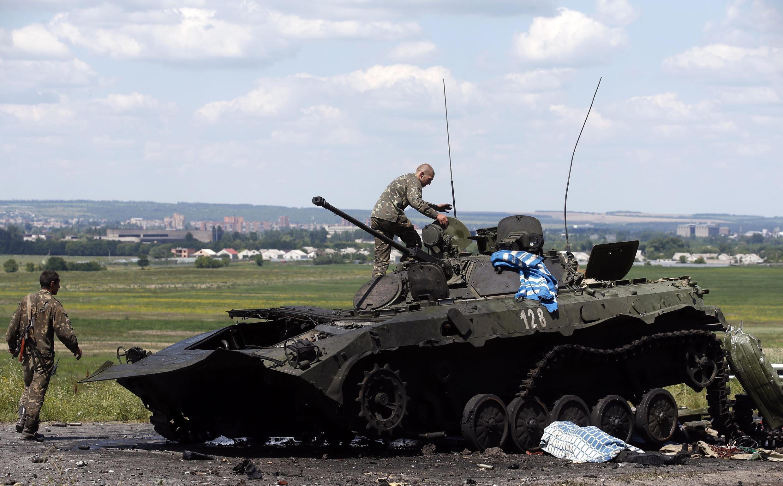 Một binh sĩ Ukraina xem xét một xe thiết giáp bị phá hủy tại Slaviansk, miền Đông Ukraina, sau khi quân nổi dậy thân Nga rút chạy. le 5 juillet 2014, après la fuite des rebelles pro-russes.
