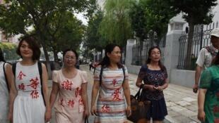 C'était en 2016, les épouses des avocats détenus portent une robe où est écrit le nom de leur mari : Li Wenzu, l'épouse de Wang Quanzhang (2e à gauche) toujours disparu, et Wang Qiaoling (droite) épouse de Li Heping, libéré en mai 2017.