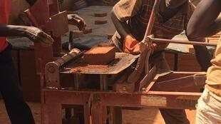 The workmen are making earth bricks by hand press, and sifting earth.