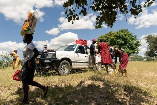 Une jeune femme vient de récupérer un sac distribué par le Programme alimentaire mondial à Mutoko, non loin de la capitale Harare. Le 13 mars 2019.