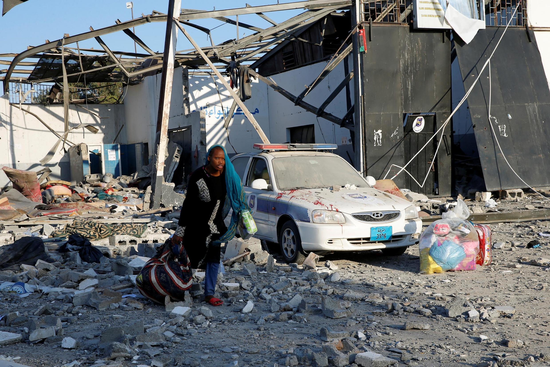 Migrante recolhe pertences no centro de refugiados de Tajura, alvo de um ataque das forças de Haftar nesta quarta-feira (3).