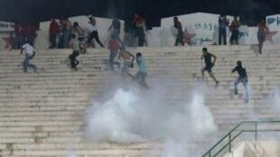 Les supporters de l'Etoile sportive du Sahel fuient des gaz lacrymogènes tirés par les forces de l'ordre lors du match face à l'Espérance Tunis.