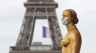 Una mascarilla adorna una estatua de la Plaza Trocadero de  París, enfrente de la Torre Eiffel, el 11 de mayo de 2020, primer día del desconfinamiento parcial en Francia
