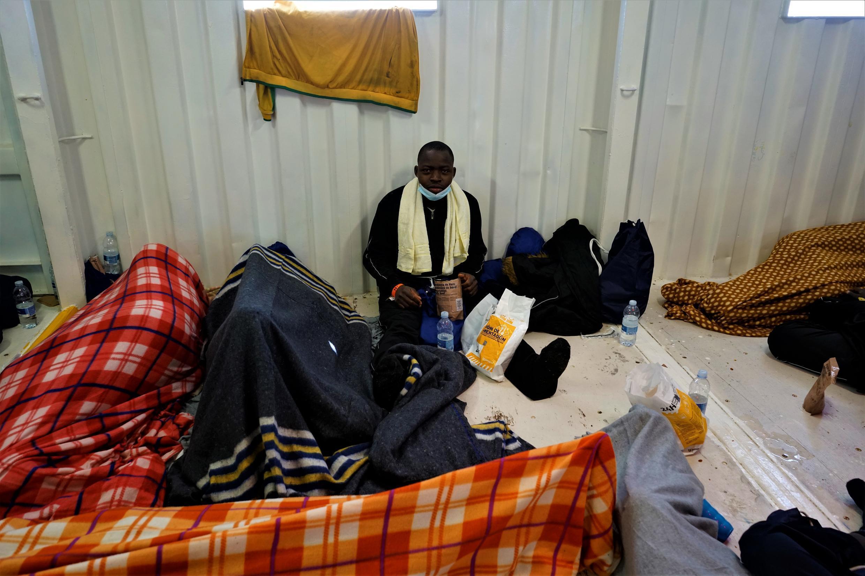 Un homme prend son déjeuner entouré de personnes en train de dormir. Crédit : RFI/Guilhem Delteil