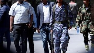 Kiongozi wa wa upinzani Jawar Mohammed kutoka jamii ya Oromo (katika shati la rangi nyeupe) anatembea akizungukwa na polisi, Oktoba 23, 2019, huko Addis Ababa, Ethiopia.